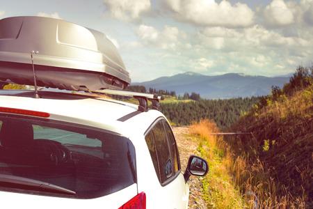 familia viaje: coche para viajar con un portaequipajes en una carretera de montaña