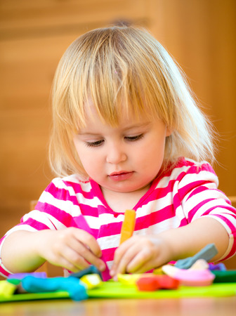 Little girl playing with plasticine at home photo