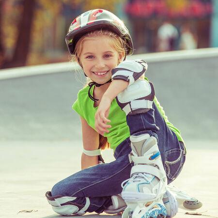 niño en patines: Niña en patines en el casco en un parque Foto de archivo