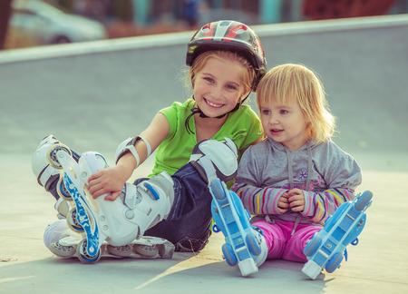 dos hermosas hermanas pequeñas en una patines sentado en la calle
