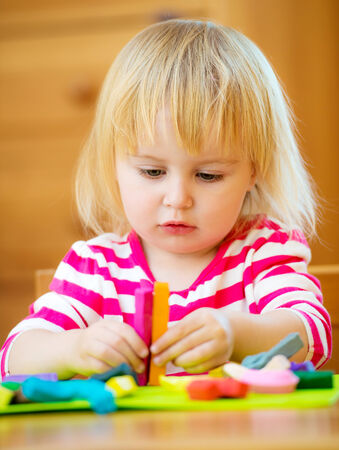 Smiling girl playing with plasticine at home photo