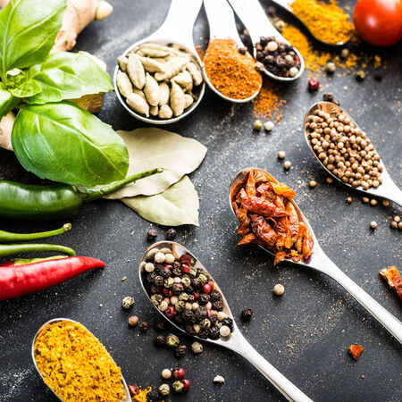 red chilly: spoons with different spices and vegetables on a black table
