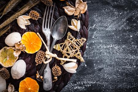 vork en lepel met kerstversiering op een zwarte geweven tafel Stockfoto
