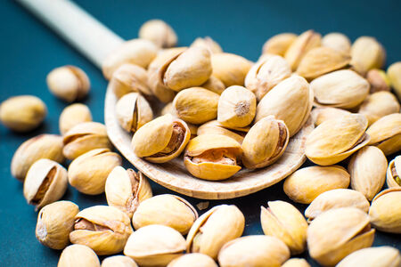 pistachios: salt pistachios in a wooden spoon Stock Photo