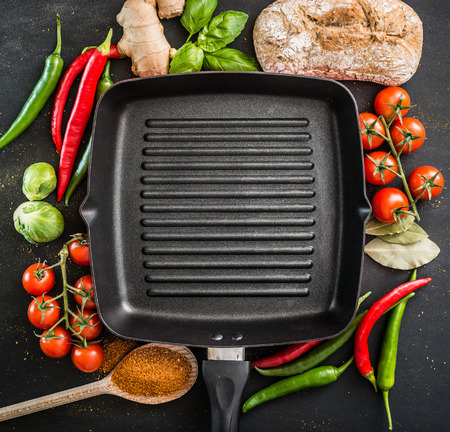 cast iron: Cast iron griddle pan on black background with vegetables