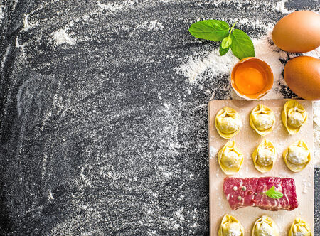 stuffed tortellini: raw ravioli and different products on the black kitchen table