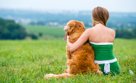 friendship: Girl with retriever on the grass