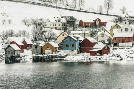 scandinavian landscape: wooden houses on the banks of the Norwegian fjord, beautiful mountain landscape in winter