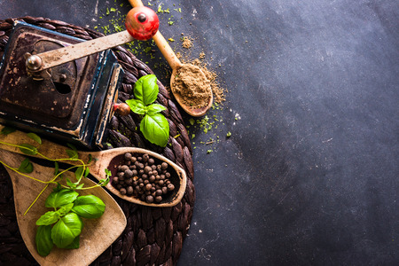 spicy cooking: old mill and wooden spoons with spices on a black table