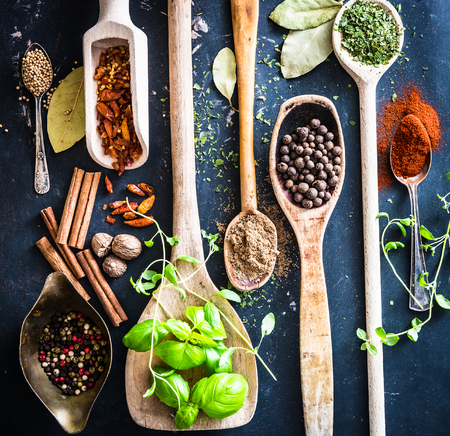 wooden spoons with spices and herbs on textured black  Stock fotó