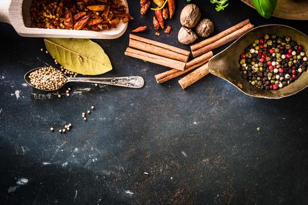 houten lepels met kruiden en specerijen op getextureerd zwarte tafel