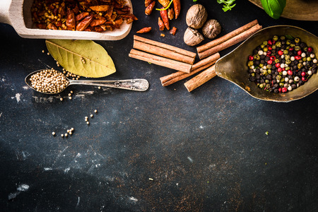 wooden spoons with spices and herbs on textured black table photo