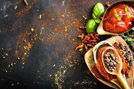 Houten lepels met kruiden en tomaten saus op een gestructureerde zwarte Stockfoto