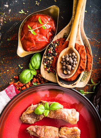 grilled meat on a plate with tomato sauce, spices on textured black  photo