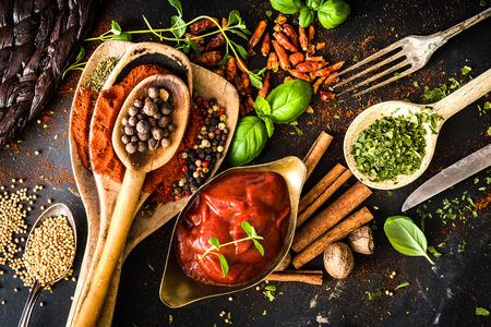 epices: sauce tomate avec des �pices et textur� table de la cuisine noire Banque d'images