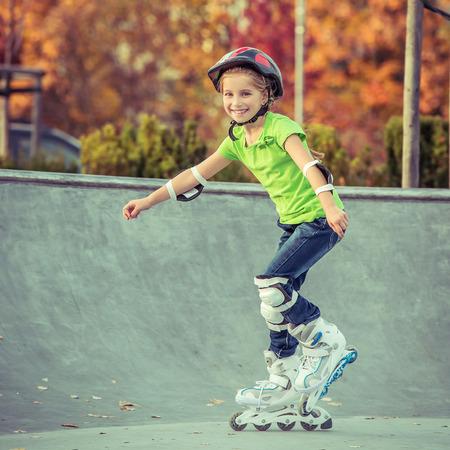 niño en patines: Niña en patines en casco en un parque Foto de archivo