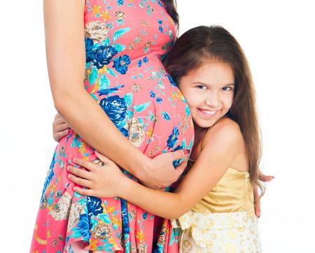Niedliche kleine Mädchen umarmt Bauch schwangeren Mutter Standard-Bild - 37040460