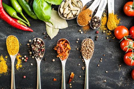 chiles picantes: cucharas con diferentes especias y verduras en una mesa de negro