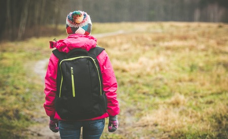 summer sport: girl with a backpack going up the path