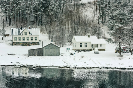 alesund: wooden houses on the banks of the Norwegian fjord, beautiful mountain landscape in winter