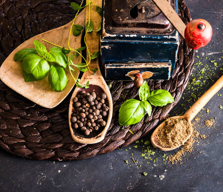 old mill and wooden spoons with spices on a black table photo