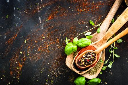 pepe nero: cucchiai di legno con le spezie e le erbe aromatiche su sfondo nero con texture