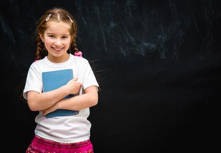schattig klein meisje glimlachend op zwarte schoolbestuur achtergrond met een blauw boek in de hand