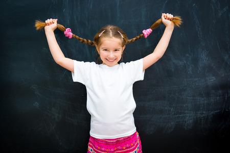 mignonne petite fille: mignonne petite fille dans une chemise blanche contre le conseil scolaire a soulev� des tresses Banque d'images