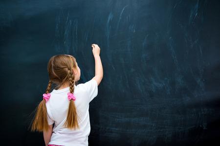 klein meisje in een wit T-shirt met staartjes schrijven met krijt op schoolbord Stockfoto