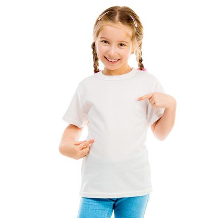 schattig klein meisje in een wit T-shirt en blauwe spijkerbroek op een witte achtergrond toont een T-shirt op