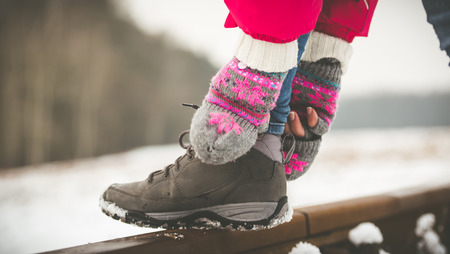 shoe laces: Girl tying shoe laces on the rails in winter Stock Photo