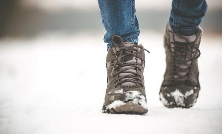 눈 덮인 길을 걷고 겨울 부츠 여자 스톡 콘텐츠