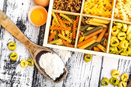 different kinds of pasta and products on textured wooden table photo