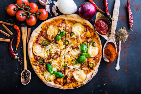 red  food: tasty pizza on a black background with spices and vegetables