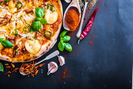 dough: tasty pizza on a black background with spices and vegetables
