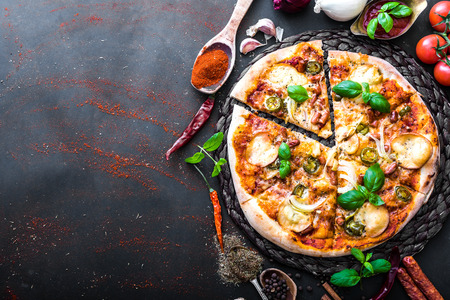 pizza: sabrosa pizza en un fondo negro con especias y verduras