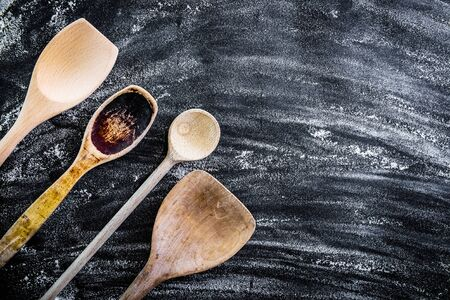 ustensiles de cuisine: wooden spoons on a black  textured table