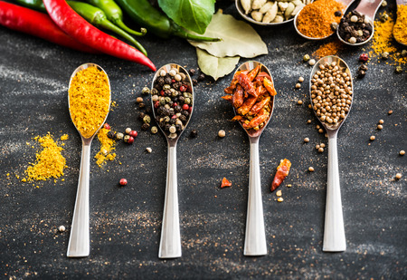 indian cooking: spoons with different spices and vegetables on a black table