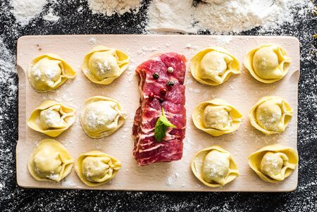 raw ravioli and different products on the black kitchen table photo