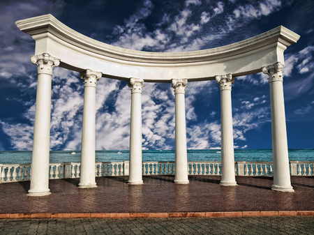 greek columns: Ancient Greek columns against a blue sky and sea Stock Photo
