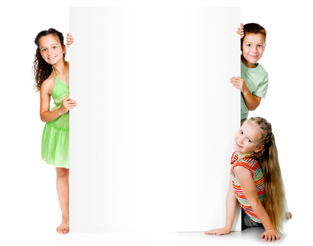 holding blank sign: Beautiful children with big white banner Stock Photo