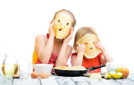 부엌에 팬케이크 요리 재미 있은 자매 스톡 콘텐츠