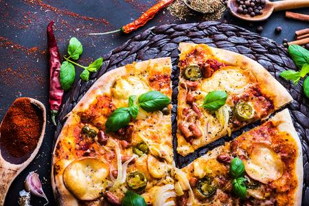 スパイスと野菜で黒の背景においしいピザ