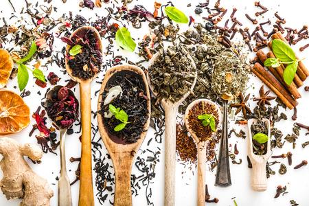 Virious druhů čaje v dřevěné lžíce na bílém stole