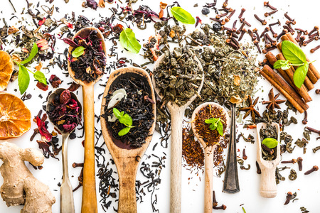 loose leaf: Virious kinds of tea in wooden spoons on white table