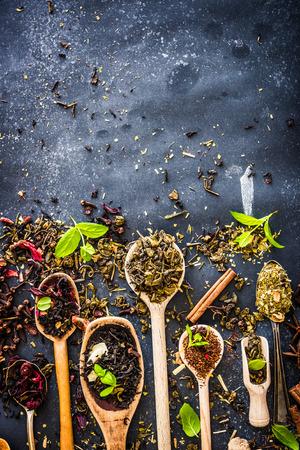 Virové druhy čaje v dřevěných lžících na černém stole