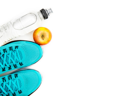 sport background: blue running shoes  and apple with objects isolated on white background photo