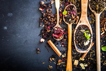 hibisco: Clases Virious de té en cucharas de madera en la mesa de negro Foto de archivo