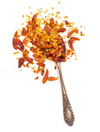 pepper flakes: dried red peppers in a spoon isolated on a white background
