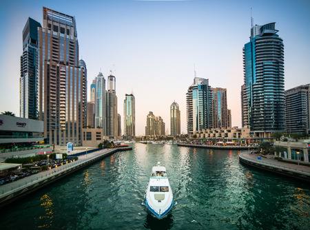 Dubai, United Arab Emirates - December 14, 2013: Modern skyscrapers and water channel with boats of Dubai Marina in evening, United Arab Emirates
